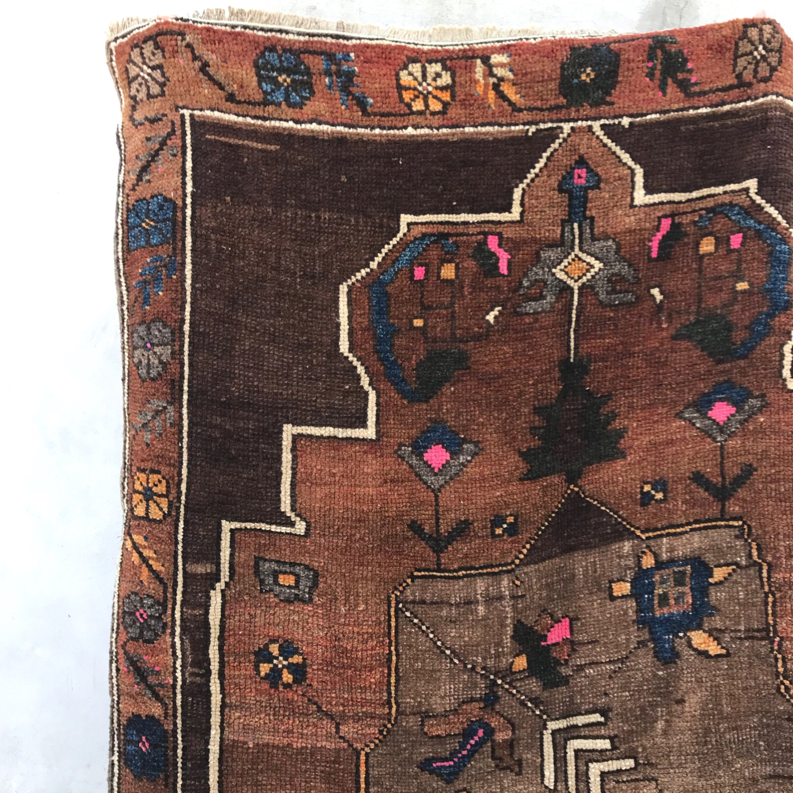 This vintage Herki Turkish rug has a beautiful shade of brown and gray. The geometric designs showcase some turtles and birds in the center motif! Pink, blue and gold accents. 4'7x7'5