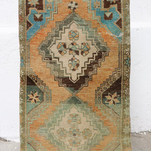 This handwoven vintage Turkish rug is a beautiful orange with teal accents. Niğde.