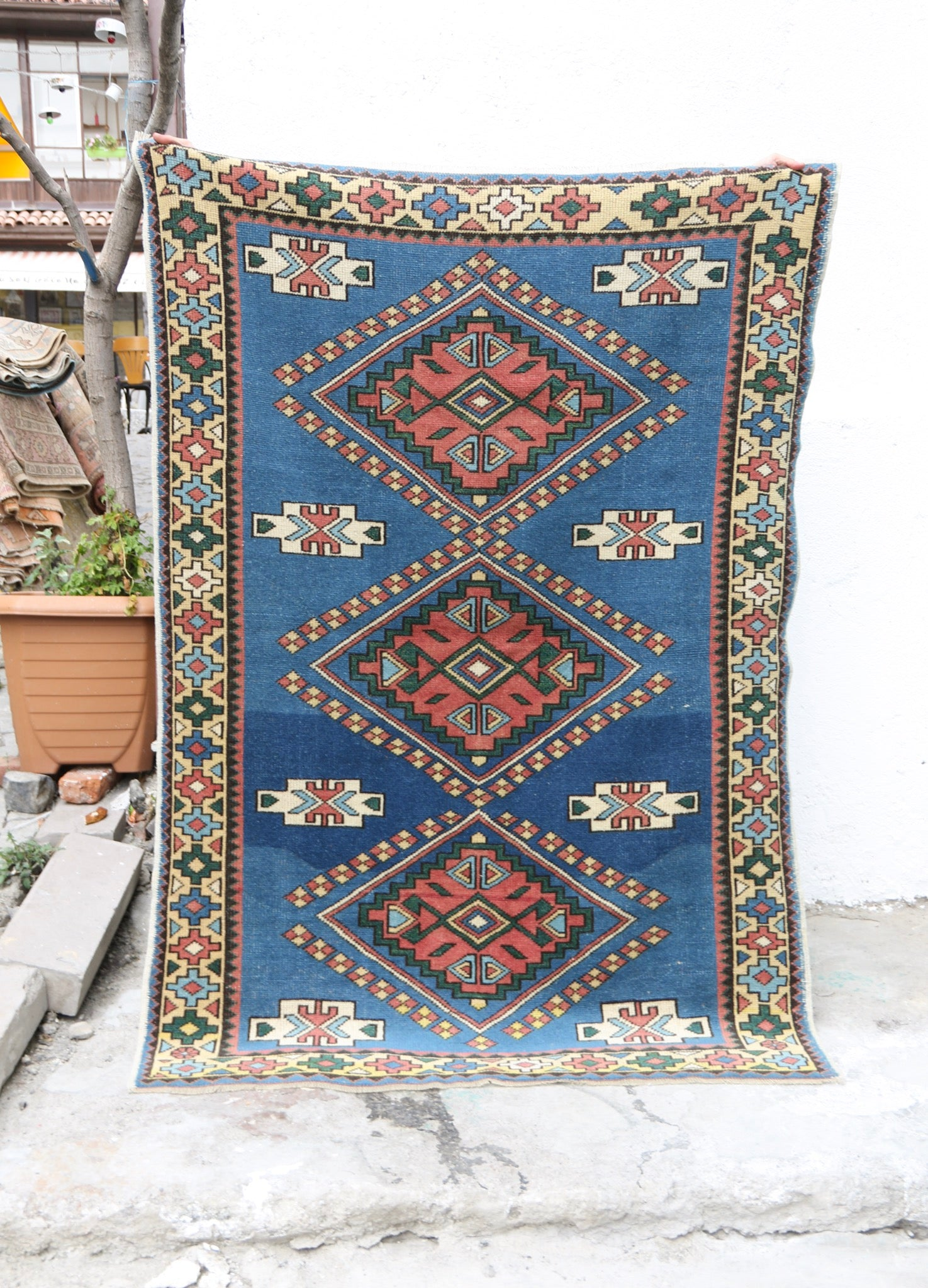 This handwoven vintage Turkish rug is has an amazing blue with dark pink and green accents. Kars.