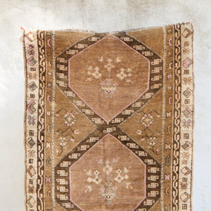 This handwoven vintage Turkish rug has beautiful warm tones of brown and pink. Sivas.