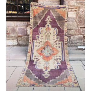 This beautiful handwoven vintage Turkish rug is a beautiful purple and peach with periwinkle accents. 4'3x9'5