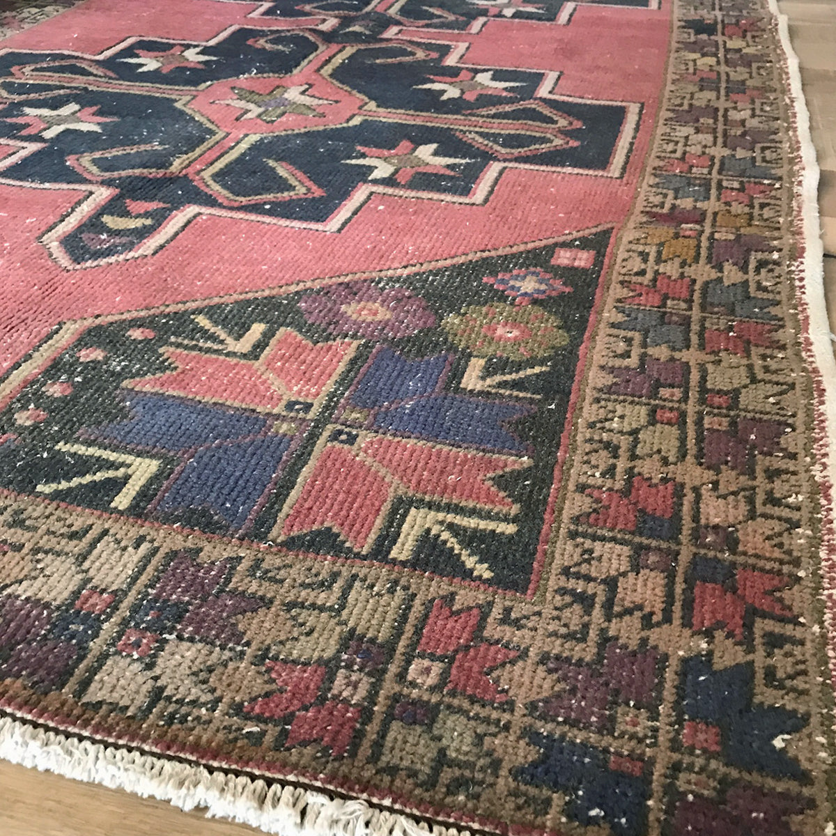 This handwoven vintage Turkish rug has salmon, pink, olive, and purple colors, and it is a great size! 53x100 inches.