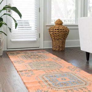 This vintage Turkish runner has a beautiful and unique orangish peach background with beautiful blue accents. 2'11x11'8