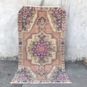 This avanoz handwoven vintage Turkish rug has an absolutely stunning blush background with purple and  blue accents. 4'1x7'5