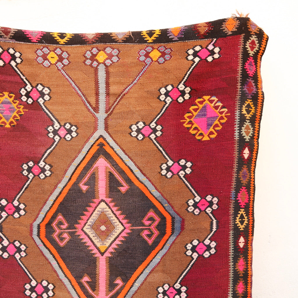 This large vintage Kars Turkish kilim has a beautiful field of a light burgundy with camel, pink, and yellow accents.