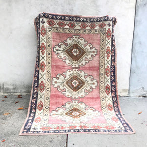 This Kars Yörük vintage Turkish rug has beautiful pinks, navy, and neutrals in a tribal design. This rugs is better in person. 5x7'4.