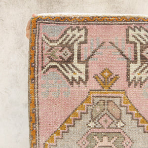 This vintage Turkish rug is a beautiful pink with yellow and soft blue accents. Great for entryways, bathrooms, kitchens and layering.