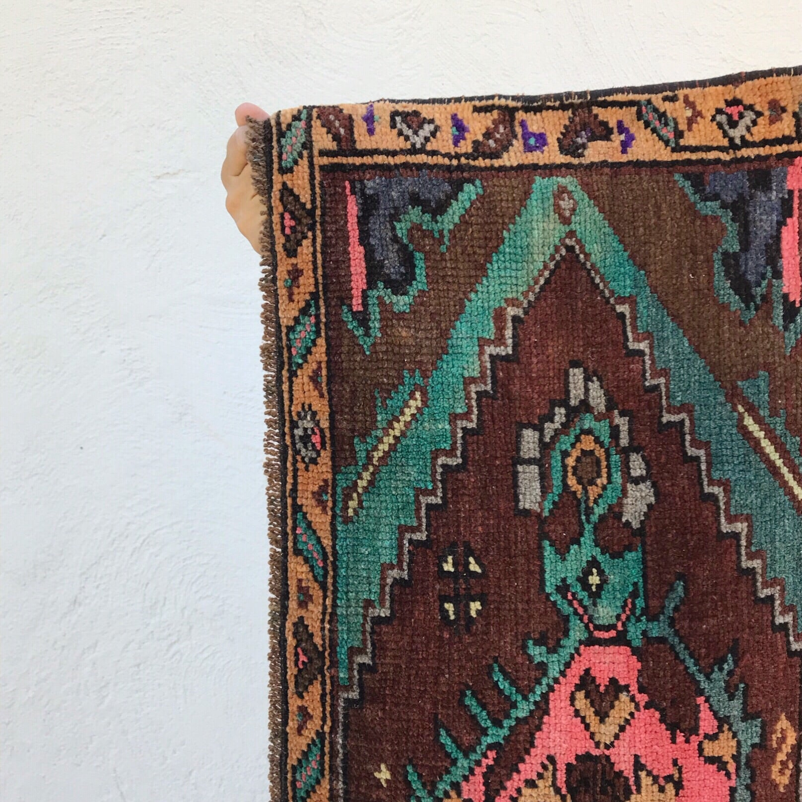This small handwoven vintage Turkish rug has beautiful pops of pink and teal on a nice brown background! Great for entryways, bathrooms, kitchens and layering. 15x40 in.