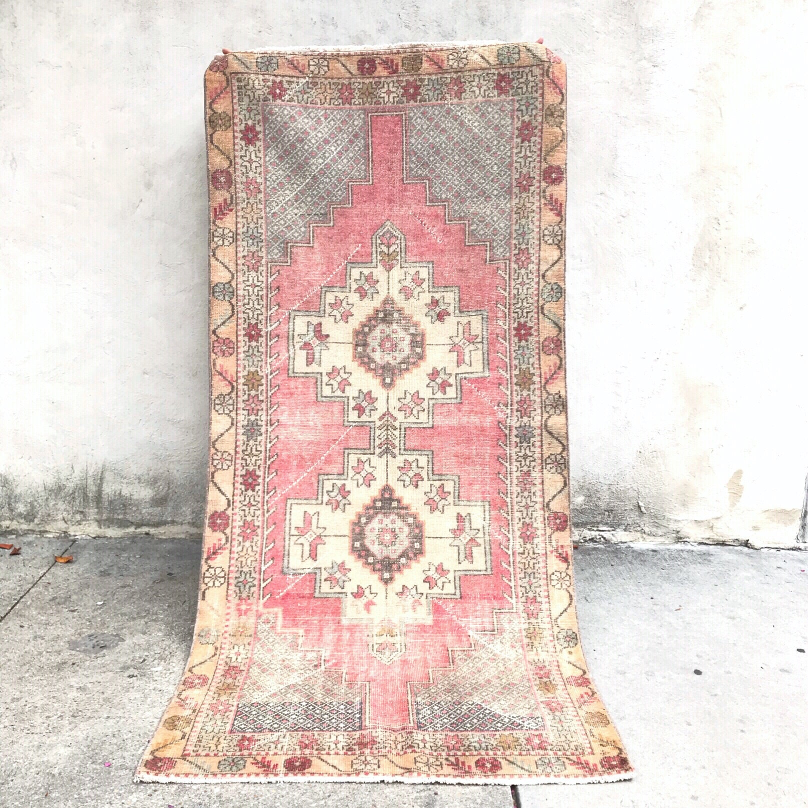 This avanoz vintage Turkish rug has a beautiful warm pink background with gray/blue and off-white accents. 3'6x7'11