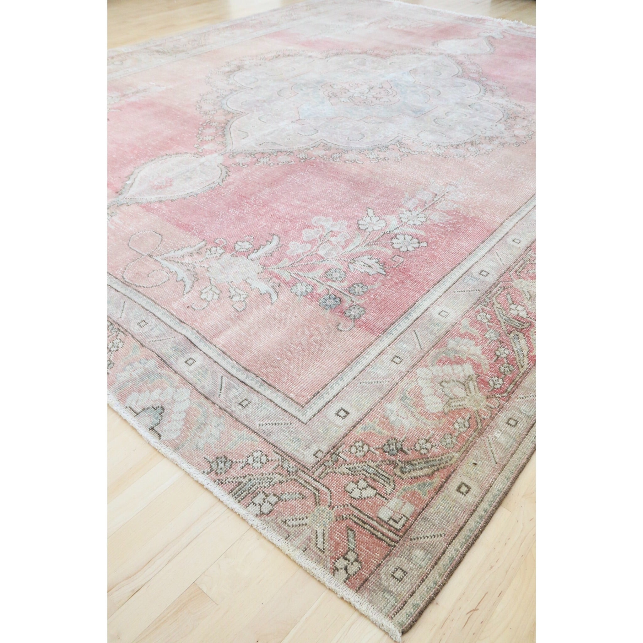This handwoven vintage Turkish rug has beautiful shades of pinks and neutral, blue and yellow accents. The detail in the rug is stunning!