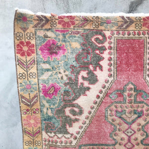 This avanoz handwoven vintage Turkish rug has an absolutely stunning pink background with soft blue accents. 3'7x7'2