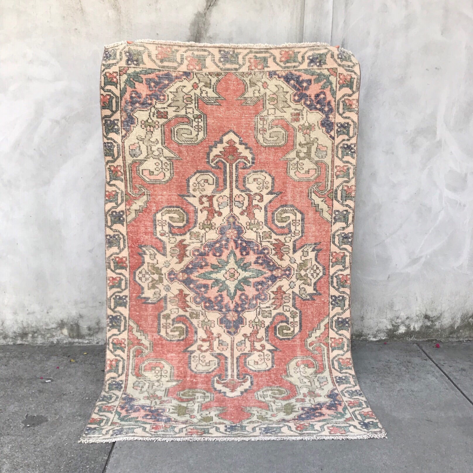 This avanoz handwoven vintage Turkish rug has an absolutely stunning pink medallion with an salmon peach background. 4'1x7'2
