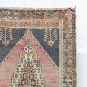 This Nigde handwoven vintage Turkish rug has a beautiful soft pink and navy with gold accents.