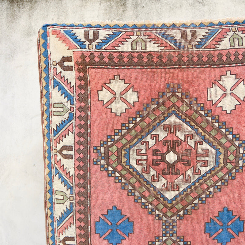 This handwoven vintage Turkish rug is a beautiful salmon pink with blue and neutral accents. Kars.