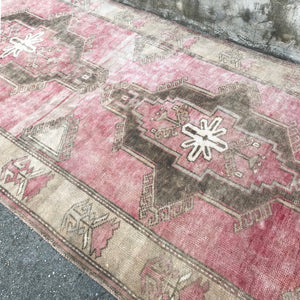 This Sivas handwoven vintage Turkish rug has a super soft pile and absolutely stunning warm pinks in its tribal design. 3'2x6'3
