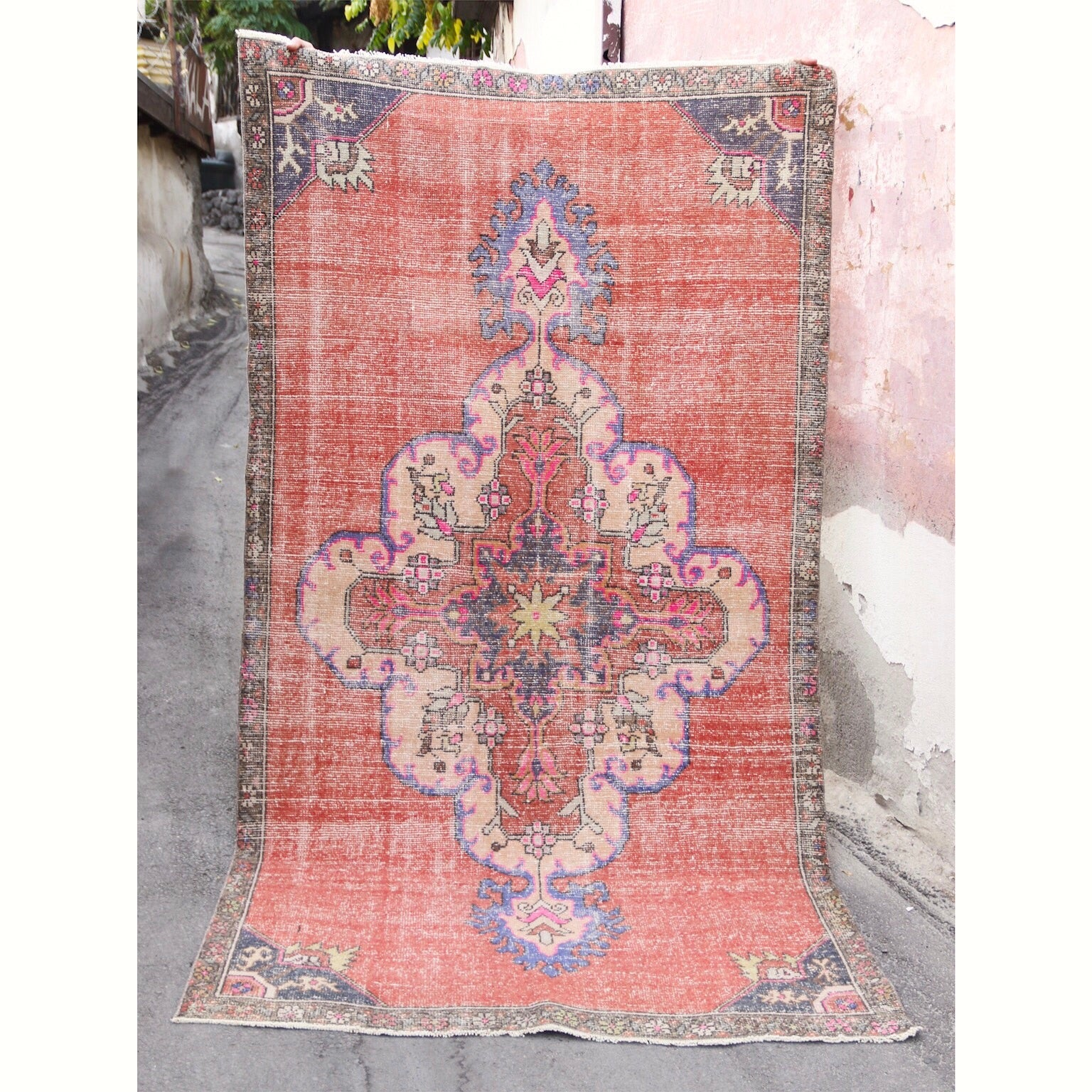 his handwoven vintage Turkish rug has amazing colors. Orange background with vibrant purple and pink accents. Konya.