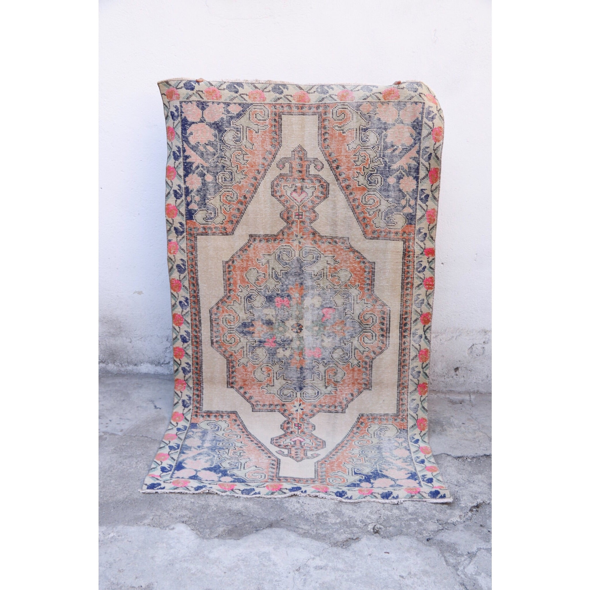 This Avanoz handwoven vintage Turkish rug has a beautiful pinks and blues on a neutral background with tangerine accents.