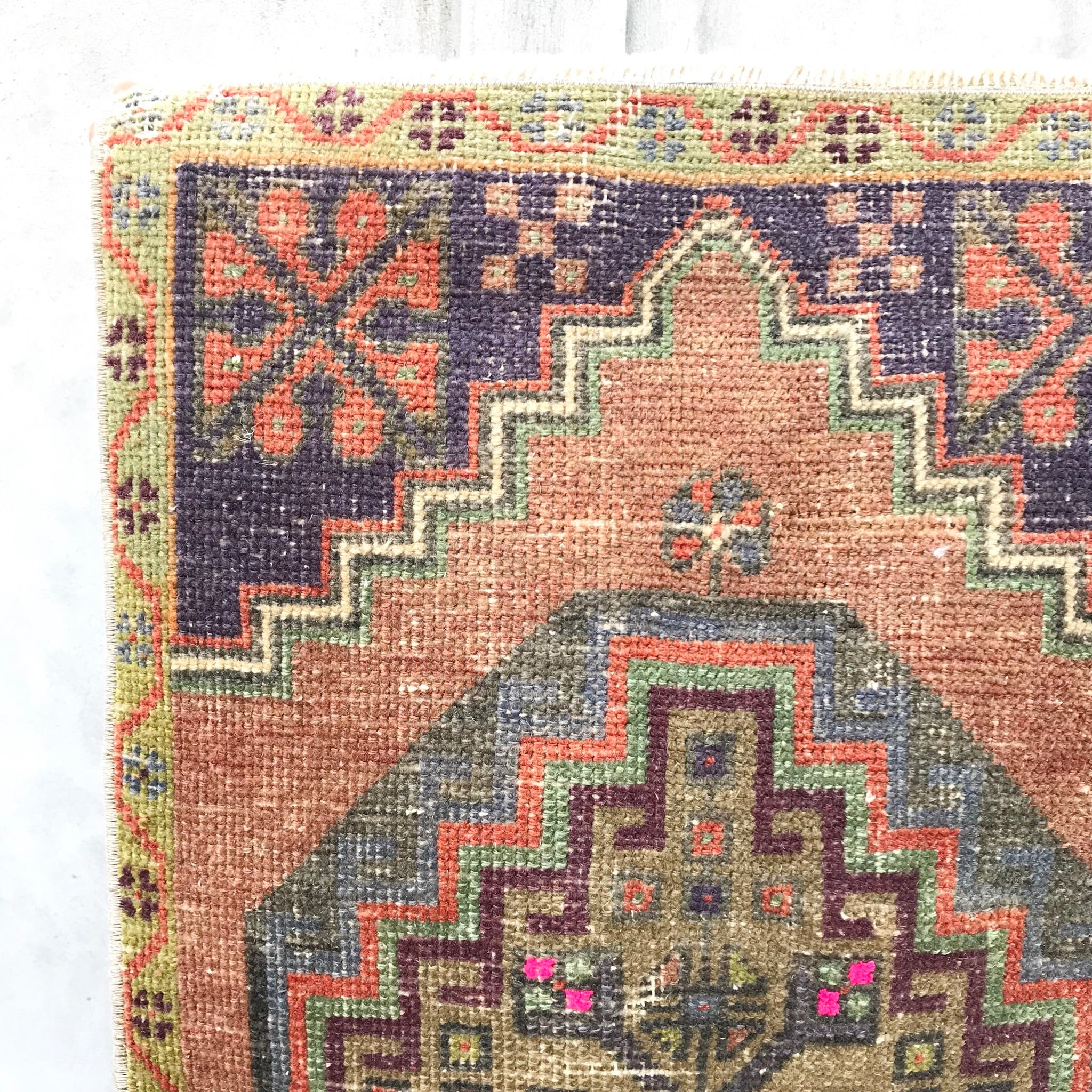 This vintage Yastik is a beautiful peach with purple hot pink accents. Great for entryways, bathrooms, kitchens and layering.