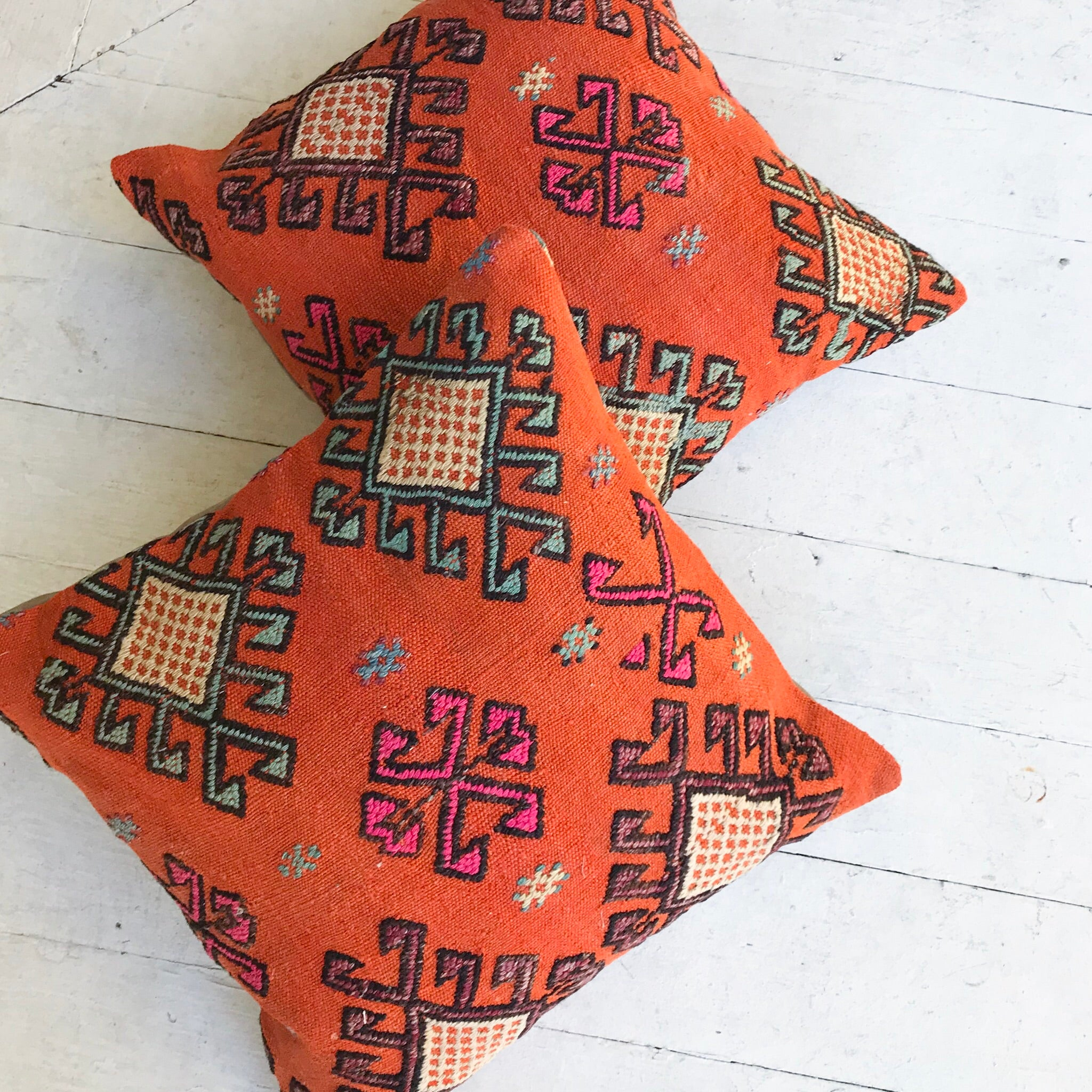 Cicim rugs have embroidery and beautiful detail. Our pillowcases are made from recycled handwoven vintage Turkish kilims.  Zipper closure. Insert not included. Natural dyes. Wool. Each pillow is one of kind.   This is a set of 2. Orange background with black, teal, pink and cream accents.