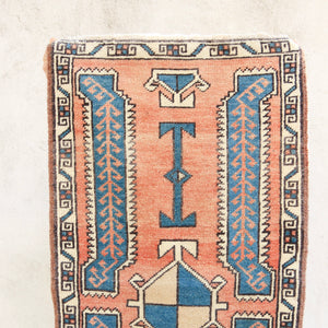 This vintage Turkish rug is a beautiful peach with blue accents. Great for entryways, bathrooms, kitchens and layering.
