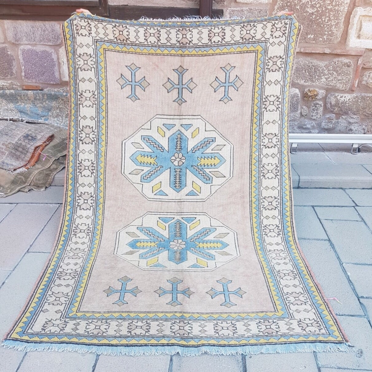 This tribal Kars Yörük vintage Turkish rug has a beautiful dusty blush/pink background with blue, yellow, and off-white accents. 4'8x7'2