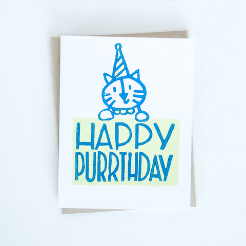 "Cat wearing a birthday hat block printed in light green and blue with words ""Happy Purrthday"" greeting card"