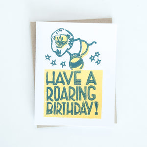 "On sale lion standing on a ball block printed in blue and yellow with words ""Have a roaring birthday!"" card"