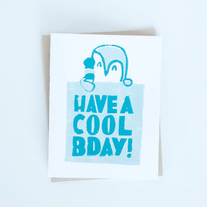 "On sale penguin holding an ice cream cone block printed in dark and light turquoise with words ""Have a cool day"" card"