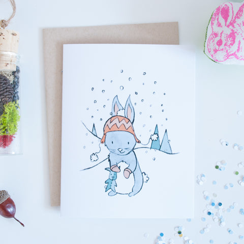 Bunny wearing a toque outside with snow falling illustrated holiday card