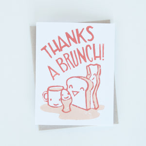 "On sale, toast, egg, bacon and cup of coffee illustration block printed in dark and light orange with words ""Thanks a brunch!"" greeting card"