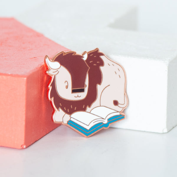Wood buffalo or bison reading a book hard enamel pin