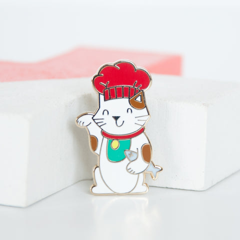 White and brown lucky cat or maneki neko cat wearing a red chef hat and holding a dead grey fish enamel pin