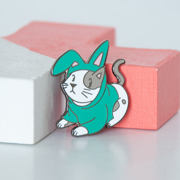 Cosplay white and grey kitty dressed in a turquoise bunny outfit hard enamel pin
