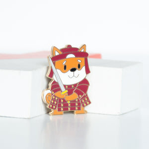 Japanese shiba dog wearing a red warrior's outfit wielding a sword enamel pin