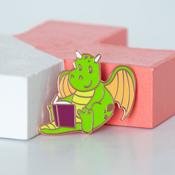 Mythical green and yellow dragon reading a book enamel pin