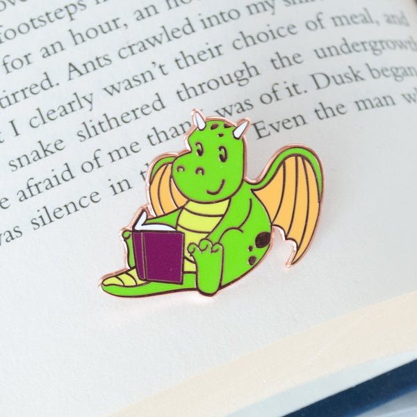 Mythical green and yellow dragon sitting and reading a book enamel pin