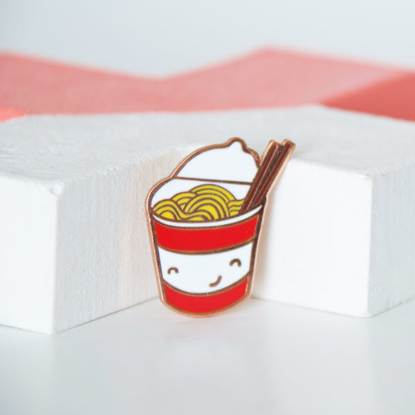 Red and white cup of instant noodles with brown chopsticks enamel pin