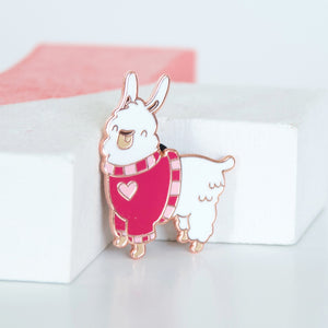 Fluffy white llama wearing a pink sweater with a pink heart enamel pin