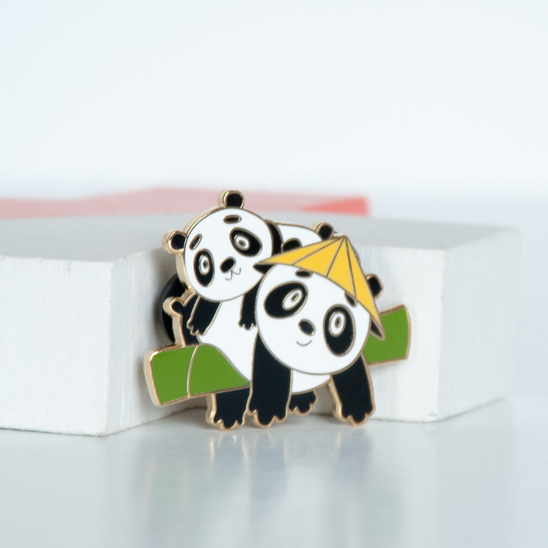 2 giant black and white pandas hanging on a bamboo branch with one panda wearing a yellow straw hat enamel pin