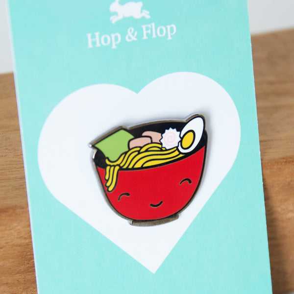 Smiling red bowl of ramen noodles enamel pin on a branded card backing