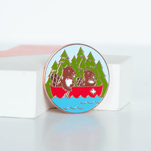 On sale, toonie sized enamel pin of 2 beavers canoeing in the lake with trees in the background.