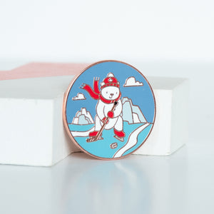 On sale white polar bear in canada coloured toque, scarf, mitts and skates playing hockey on ice with ice bergs in the background of a circle sized enamel pin