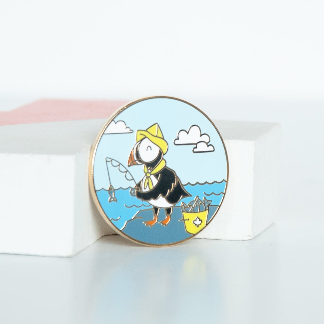 On sale east coast puffin dressed in a yellow fisherman's hat fishing in the ocean with clouds and blue sky background. A Circle hard enamel pin