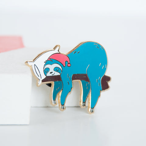 Blue sloth wearing a red cap and sleeping on a white pillow and branch enamel pin