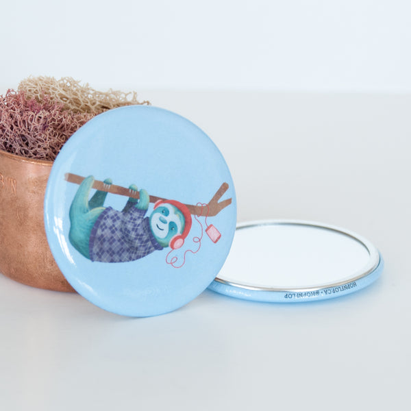 Sloth listing to music and hanging off a branch on a blue background illustrated travel pocket mirror