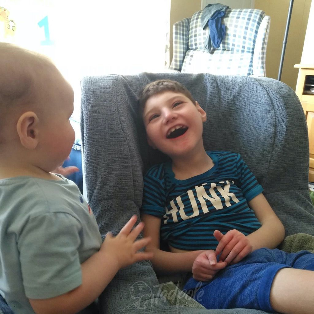 Brothers interacting at home, with smiling boy in his Chillout Rock'er.