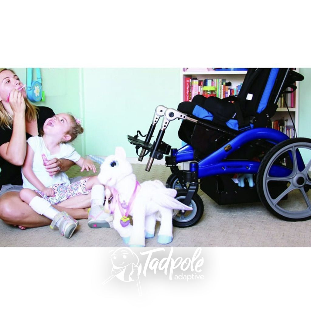 Mom and daughter playing on floor with Convaid Flyer Tilt-in-Space Wheelchair in background.