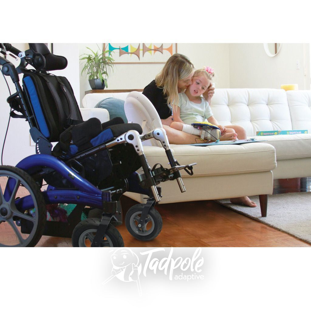 Mom an daughter chilling on couch with Convaid Flyer Tilt-in-Space Wheelchair in foreground.