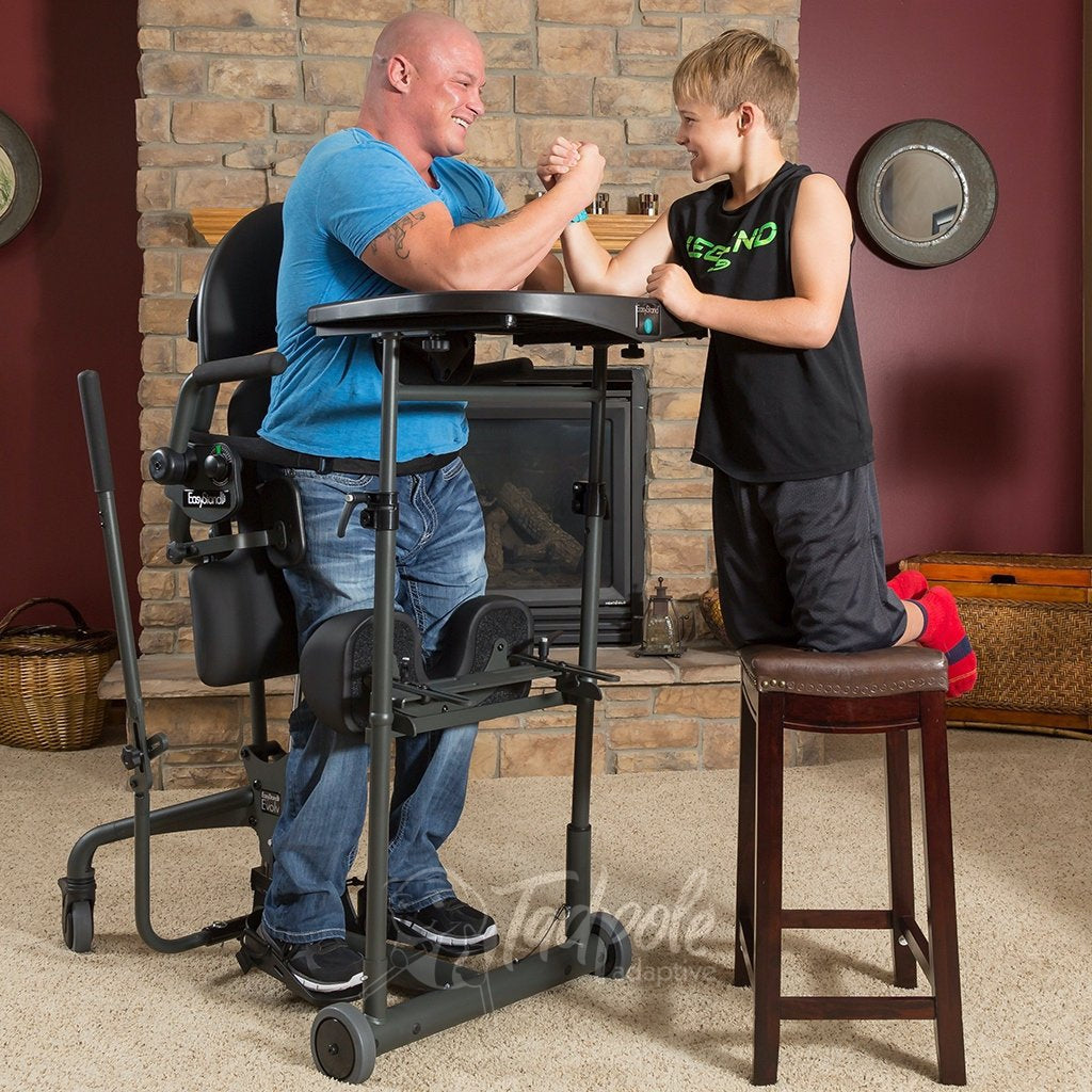 EasyStand Evolv Large. At home, man arm wrestling with kiddo