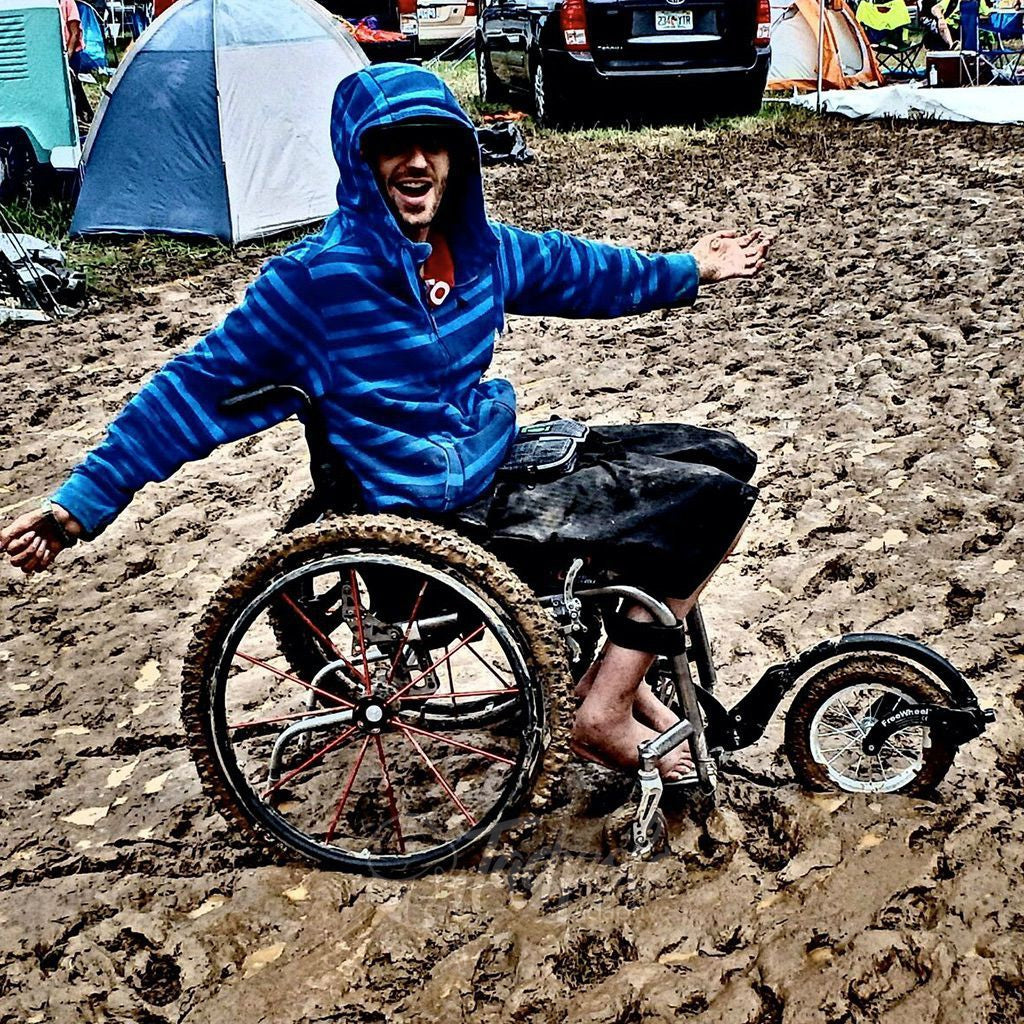 Young man, deep in the mud, but mobile in his FreeWheel Wheelchair Attachment.